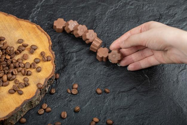 블랙에 초콜릿 사탕을 복용하는 손. 무료 사진