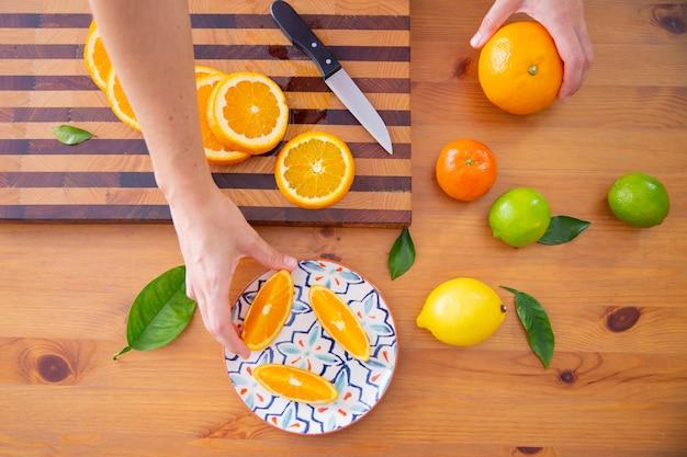 Mano prendendo pezzo di arancia dal piatto di ceramica Foto Gratuite
