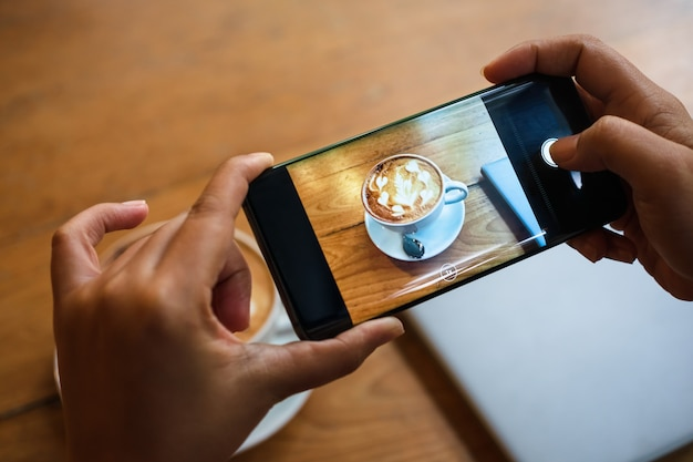 Hand taking a picture of hot latte art coffee cup with art foam on wooden table Premium Photo