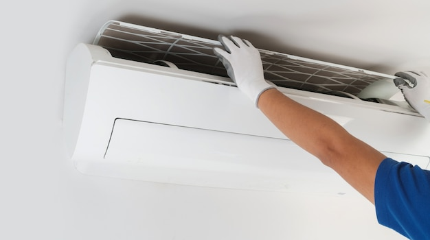 Hand of technician cleaning air conditioner in house Premium Photo