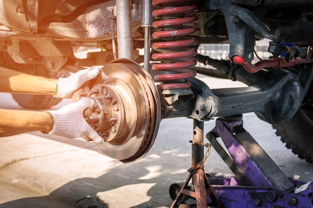 Hand technician wearing gloves, repairing car brake. Premium Photo