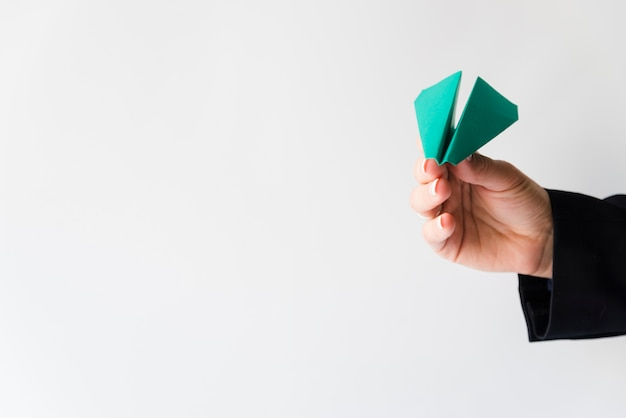Hand throwing green paper plane Free Photo