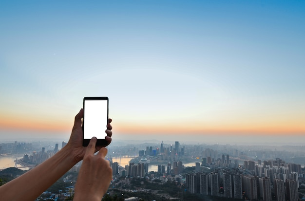 Hand Touching A Mobile Screen With City Background Photo