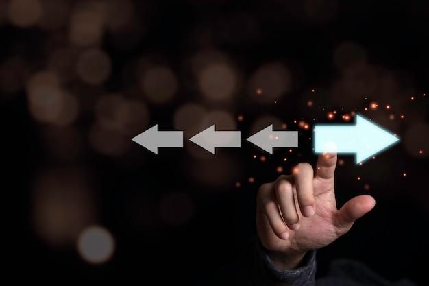 Рука, касающаяся светло-синей стрелки, которая противоположна белому. разрушение и различное мышление для открытия новой технологии и новой концепции бизнес-возможностей. Premium Фотографии