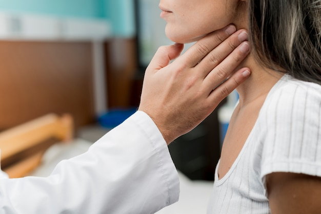 Hand touching throat of patient Free Photo