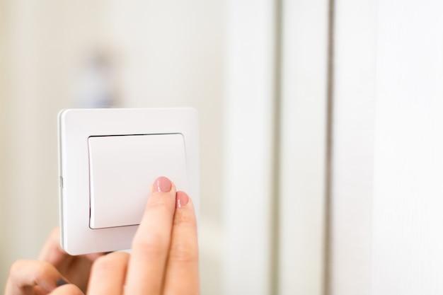 Hand turning wall light switch Premium Photo