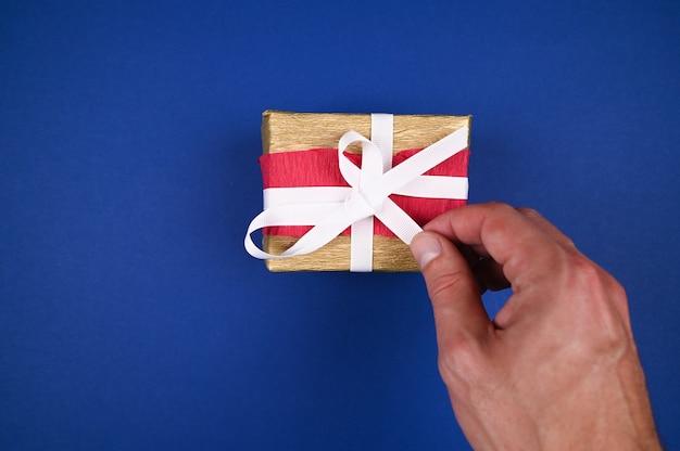 Рука распаковывает крупный план новогоднего подарка. Premium Фотографии