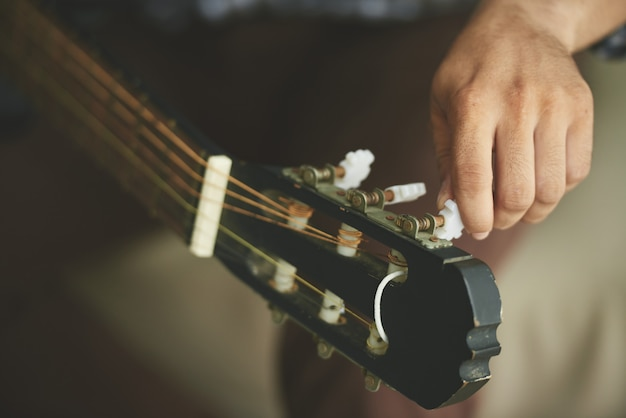 Hand of unrecognizable man turning tuning pegs of acoustic guitar Free Photo