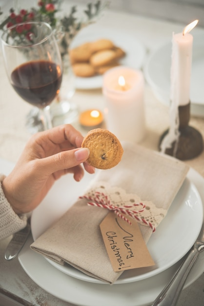 Hand of unrecognizable woman holding cookie against table set up for christmas dinner Free Photo