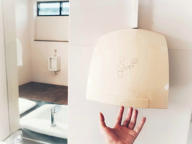 Hand using automatic hand dryer after toilet for hygiene. Premium Photo