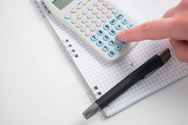 Hand using calculator on desk Free Photo