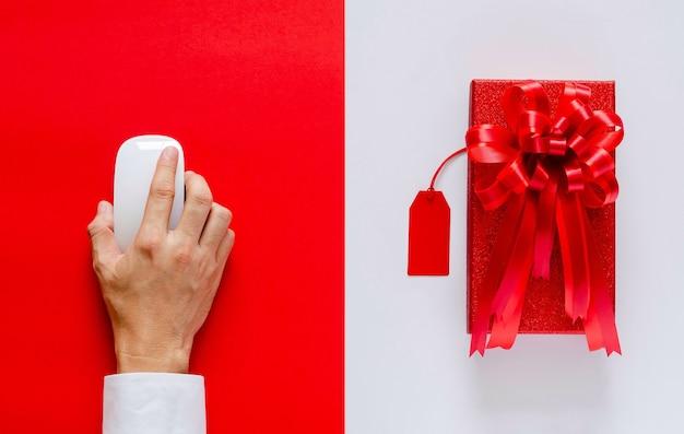 Рука, использующая мышь, делающая покупки в интернете с красной рождественской коробкой и ценником на белом и красном Premium Фотографии