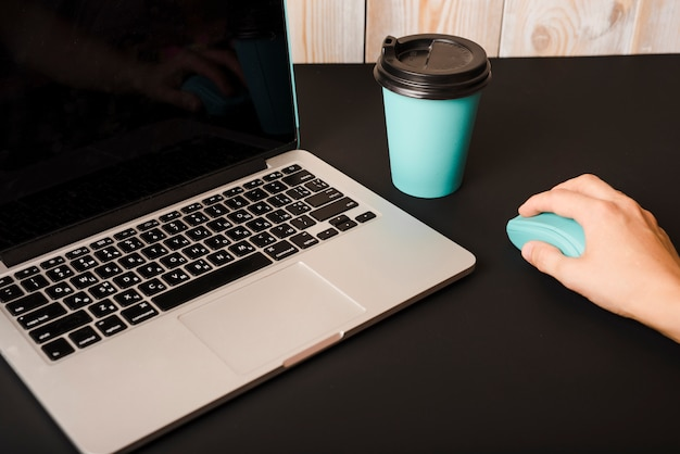 Hand using mouse with takeaway coffee cup and laptop on black desk Free Photo