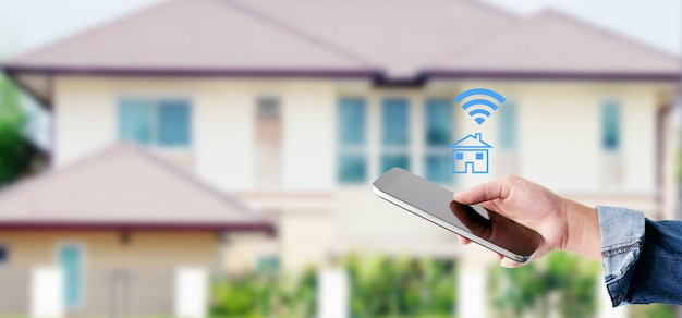 Hand using smart phone with smart home control icon over blur house background, smart home control concept Premium Photo