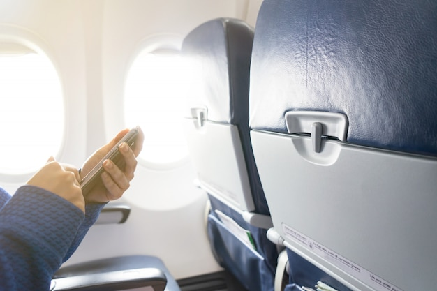 Hand using smartphone and window in airplane with seats in the cabin Premium Photo