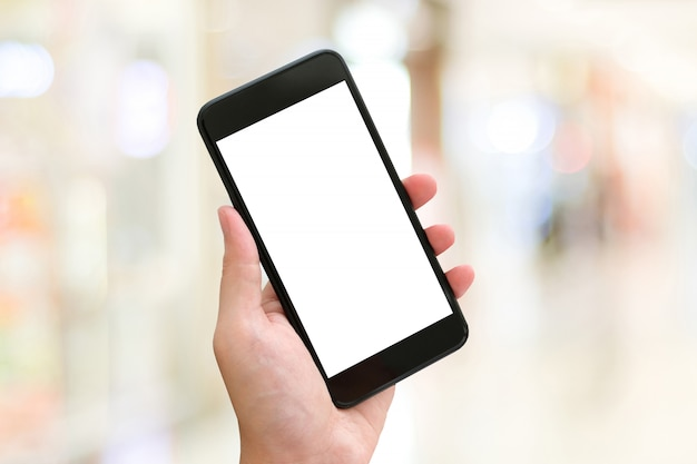 Hand using smartphone with blank screen over blur bokeh light background Premium Photo
