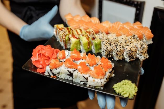ハンドウェイターセット伝統的なレストランで美味しい新鮮な寿司スレートプレート、日本の刺身を保持しています。フィラデルフィアの新鮮なロールパンは、寿司バーのプレートで提供しています。手袋のウェイターが巻き寿司を保持しています。 Premium写真