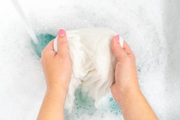 Hand washing white clothes in sink to bleach Premium Photo