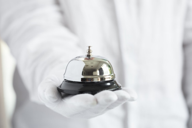 Hand in white gloves holding hotel bell Premium Photo