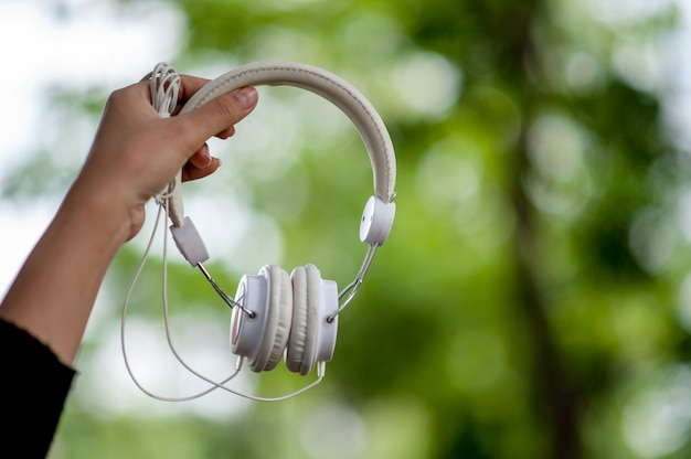 Hand and white headphones, devices for listening to music Premium Photo