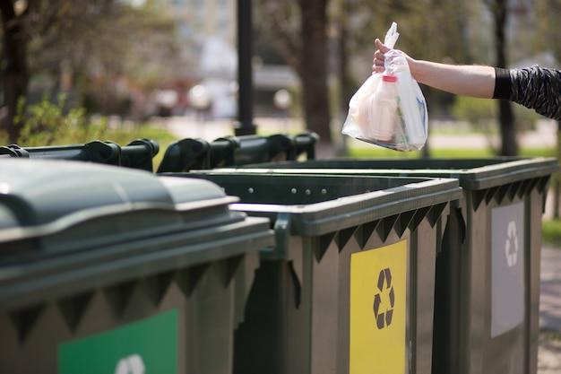 Рука с пакетом пластикового мусора над контейнерами для разделения и сортировки стекла Premium Фотографии