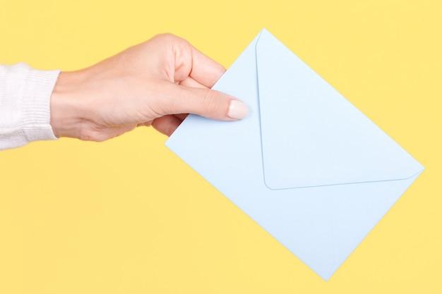 Рука с синим бумажным конвертом изолированы Premium Фотографии