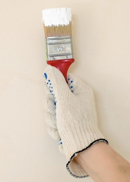 Hand with brush in white paint Premium Photo