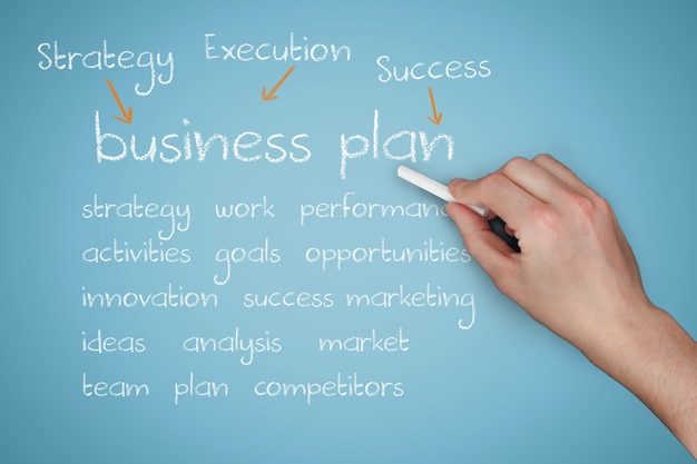 Hand with chalk explaining business plan Free Photo