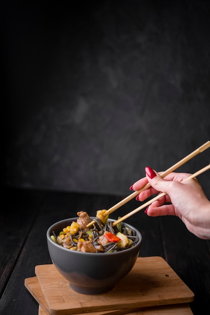 Hand with chopsticks mixing in noodles bowl Free Photo