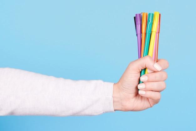 Рука с цветными фломастерами изолированы Premium Фотографии