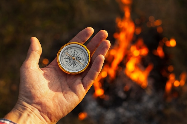 Hand with compass and fire flames along Free Photo