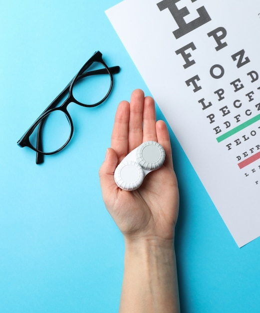 Hand with contact lenses, glasses and eye test chart on blue surface, top view Premium Photo
