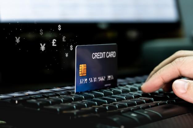 Рука с кредитной карты на клавиатуре с потоком значок валюты деньги. Premium Фотографии
