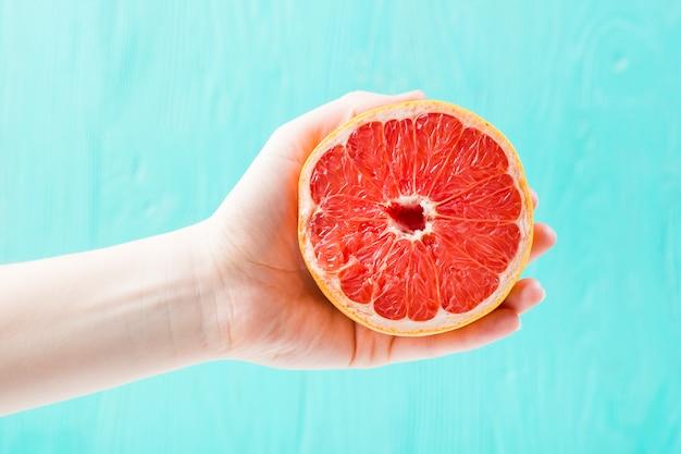 Hand with fresh grapefruit Free Photo