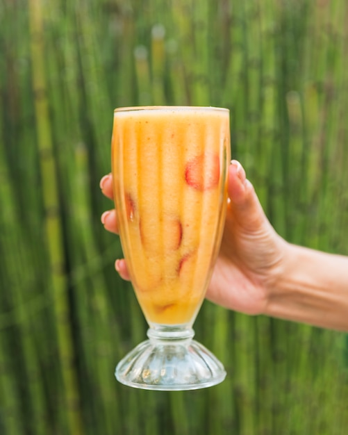 Hand with glass of fresh smoothie near bamboo Free Photo