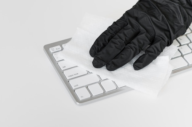 Hand with glove disinfecting keyboard surface Premium Photo