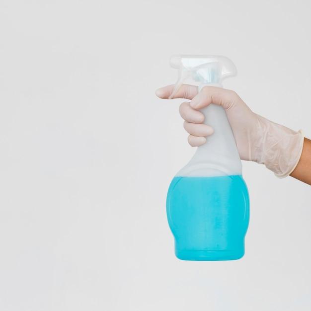 洗浄液ボトルを保持している手袋を持った手 無料写真