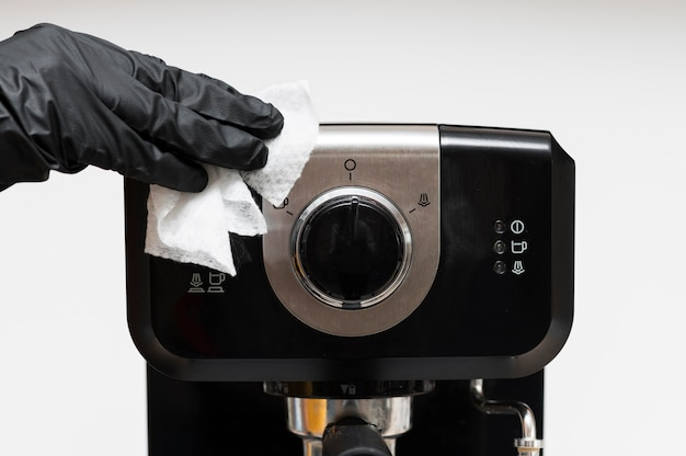 Hand with gloves disinfecting espresso machine Premium Photo