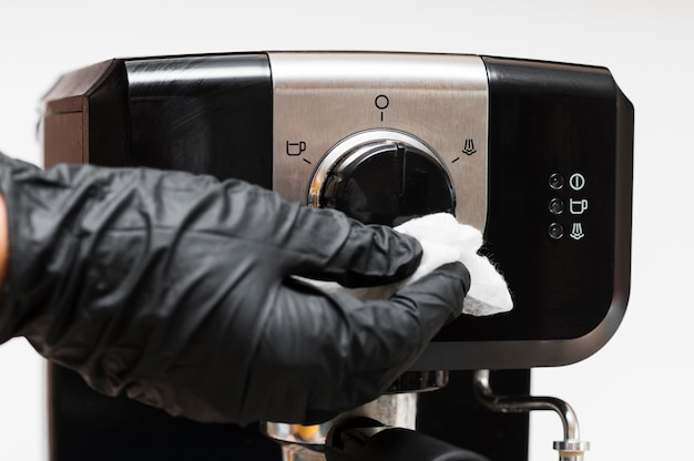 Hand with gloves disinfecting instant coffee machine Premium Photo
