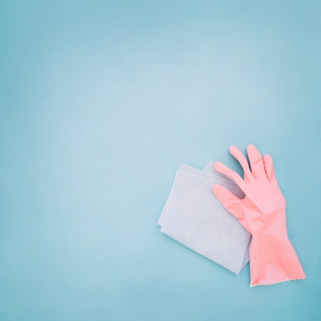 Hand with gloves holding blue dustpan Free Photo