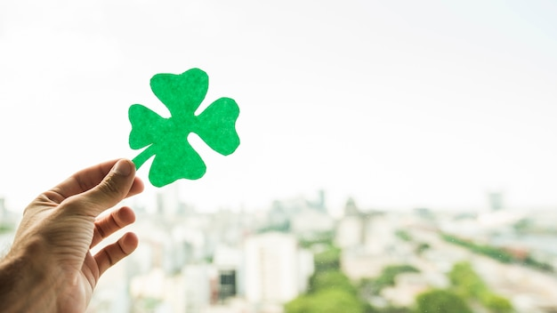 Hand with green paper shamrock and view of cityscape Free Photo