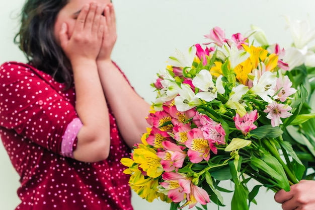 A  hand with a lush bouquet of flowers extends flowers to a woman Premium Photo