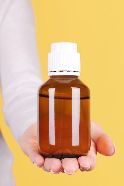 Рука с бутылкой медицины, контейнер для химии изолирован Premium Фотографии