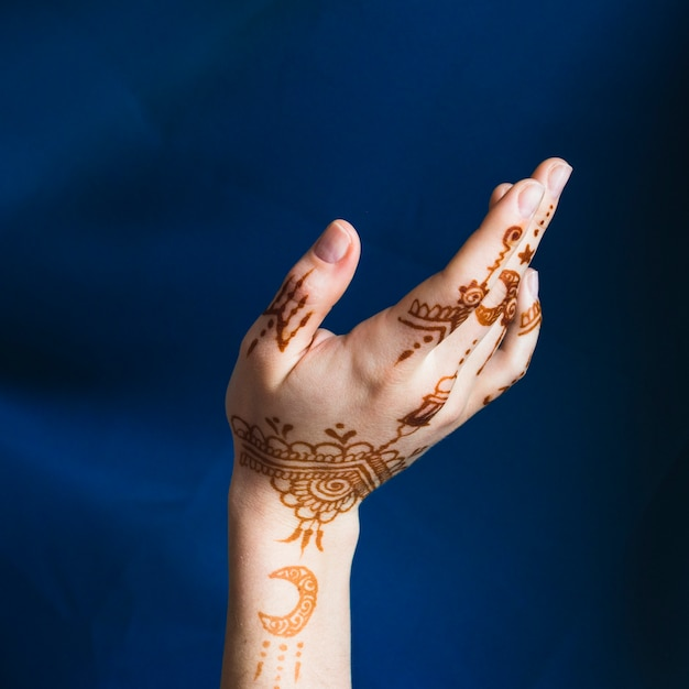 Hand with mehndi near blue textile Free Photo