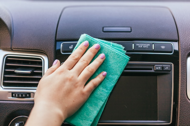 Hand with microfiber cloth cleaning car Premium Photo