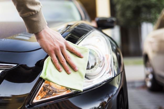 Hand with napkin cleaning headlight of dark auto Premium Photo