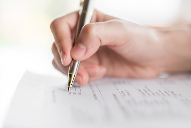 Hand with pen over application form . Free Photo