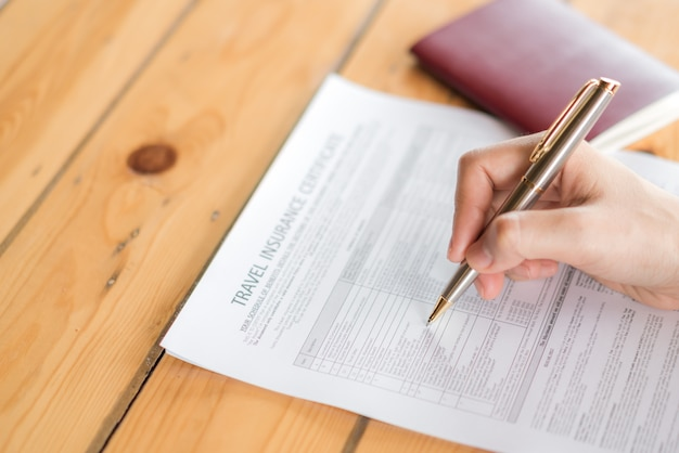 Hand With Pen Over Travel Aviation Insurance Application Form And