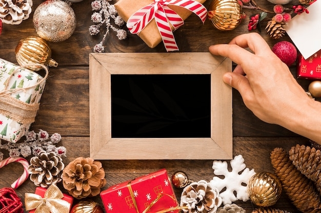 Hand with photo frame between christmas decorations Free Photo
