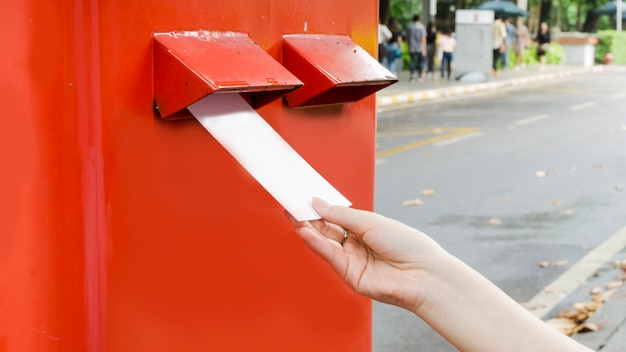 Hand with postcard and drop in red mail postbox Premium Photo